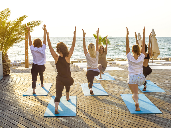Group yoga exercise by the beach during sunset